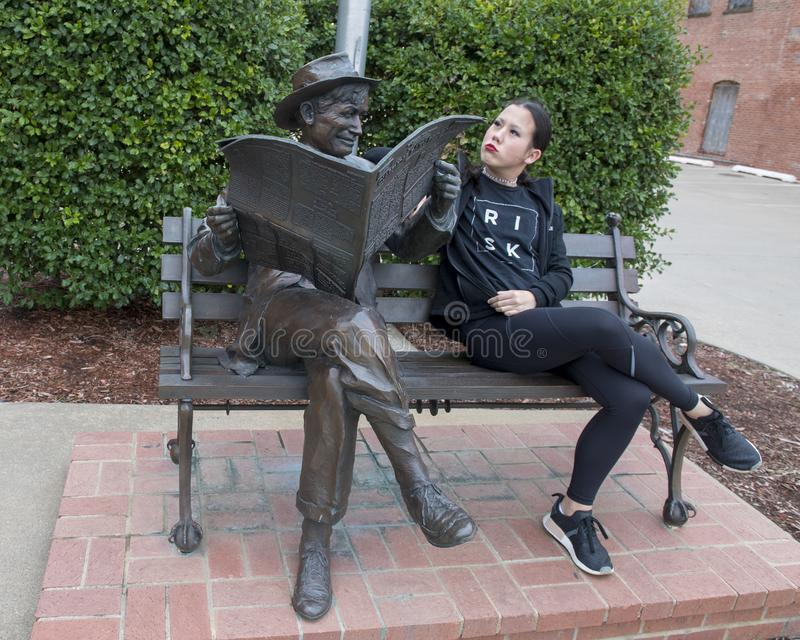 Thirteen year-old girl posing humorously with bronze of Will Rogers on a bench, Claremore, Oklahoma stock photography