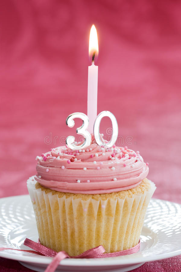 Thirtieth birthday cupcake. Mini thirtieth birthday cake decorated with a single candle royalty free stock photo