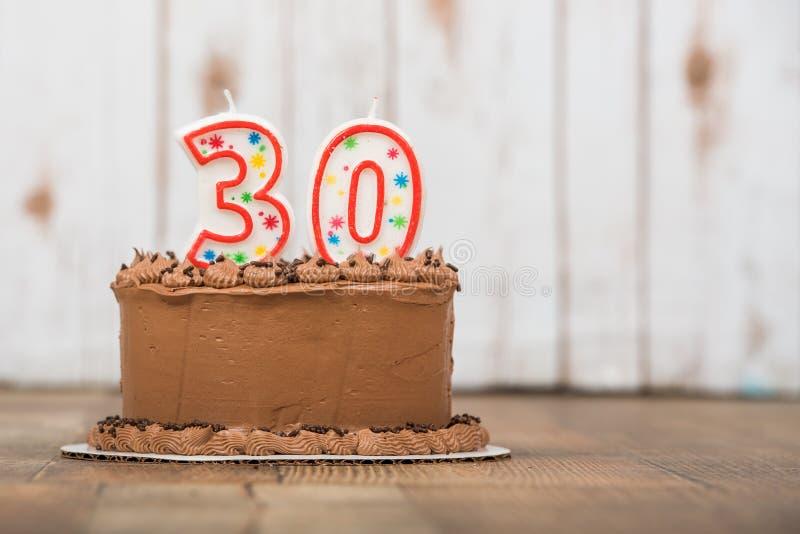 Thirtieth chocolate frosted birthday cake. Chocolate frosted cake with 30 or thirty candles on it stock photos