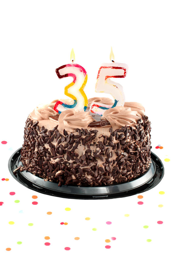 Thirty fifth birthday or anniversary. Chocolate birthday cake surrounded by confetti with lit candle for a thirty fifth birthday or anniversary celebration royalty free stock image