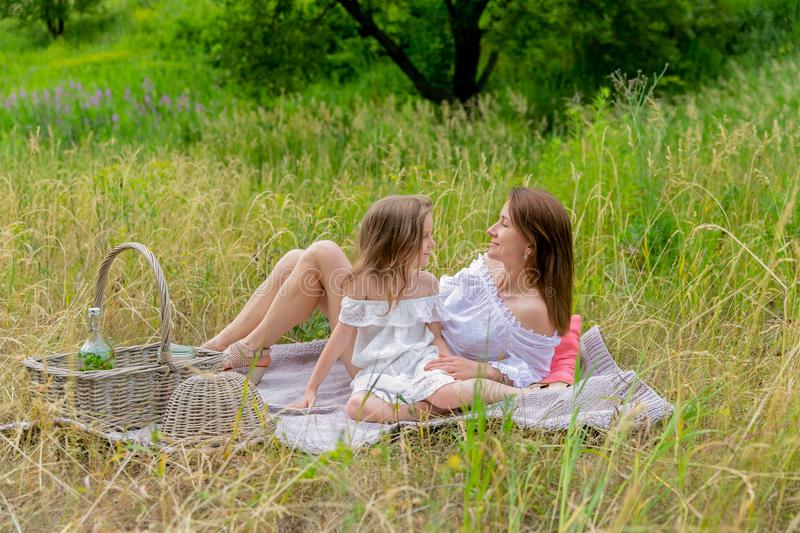 Thirty-year-old beautiful young mother and her little daughter in white dress having fun in a picnic. They are sitting on a plaid. On the grass and smiling stock image