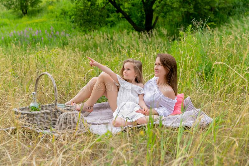 Thirty-year-old beautiful young mother and her little daughter in white dress having fun in a picnic. They are sitting on a plaid stock photography