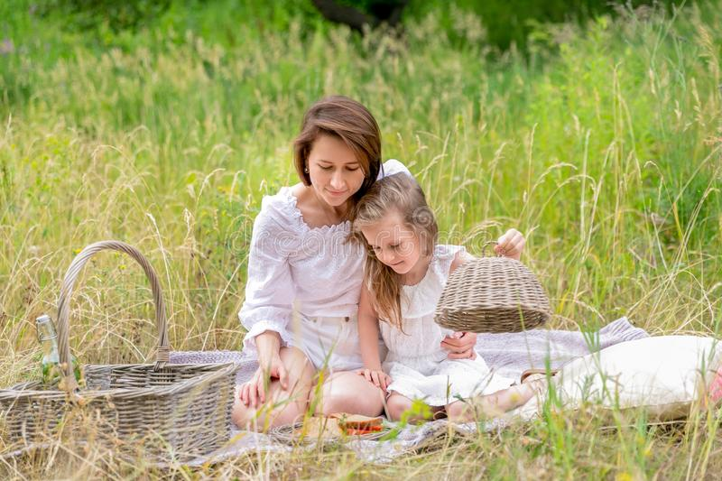 Thirty-year-old beautiful young mother and her little daughter in white dress having fun in a picnic. They are sitting on a plaid. On the grass and taking out royalty free stock image