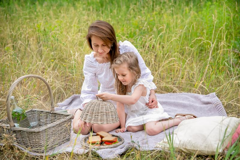 Thirty-year-old beautiful young mother and her little daughter in white dress having fun in a picnic. They are sitting on a plaid. On the grass and taking out royalty free stock photography