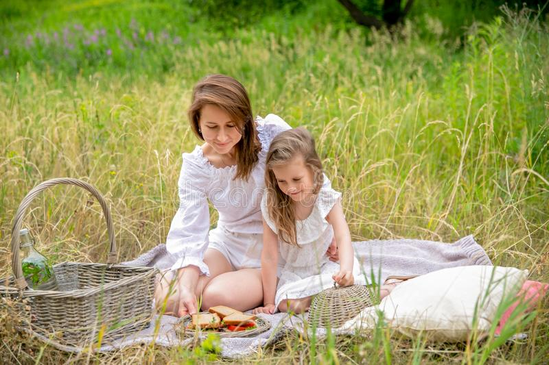 Thirty-year-old beautiful young mother and her little daughter in white dress having fun in a picnic. They are sitting on a plaid. On the grass and taking out stock photography