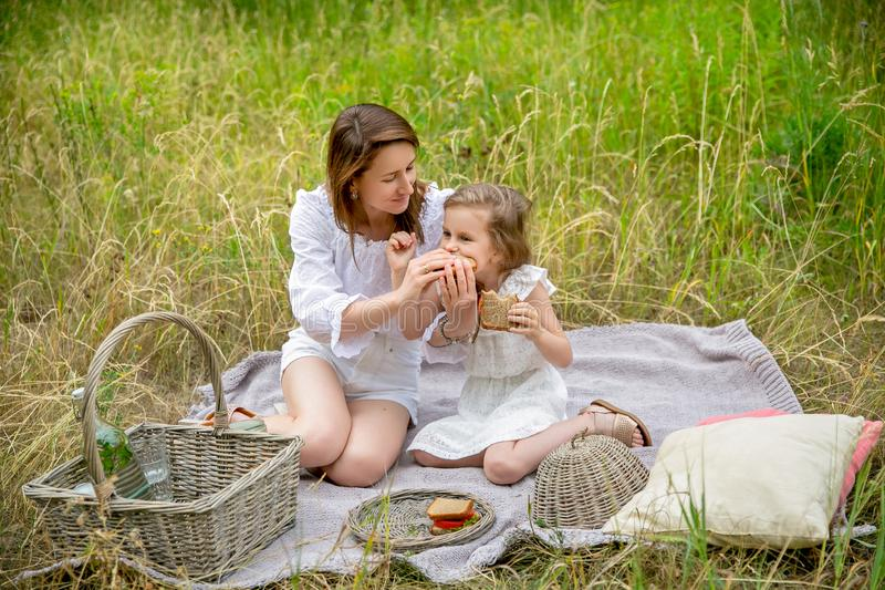 Thirty-year-old beautiful young mother and her little daughter in white dress having fun in a picnic. They are sitting on a plaid. On the grass eating stock photo