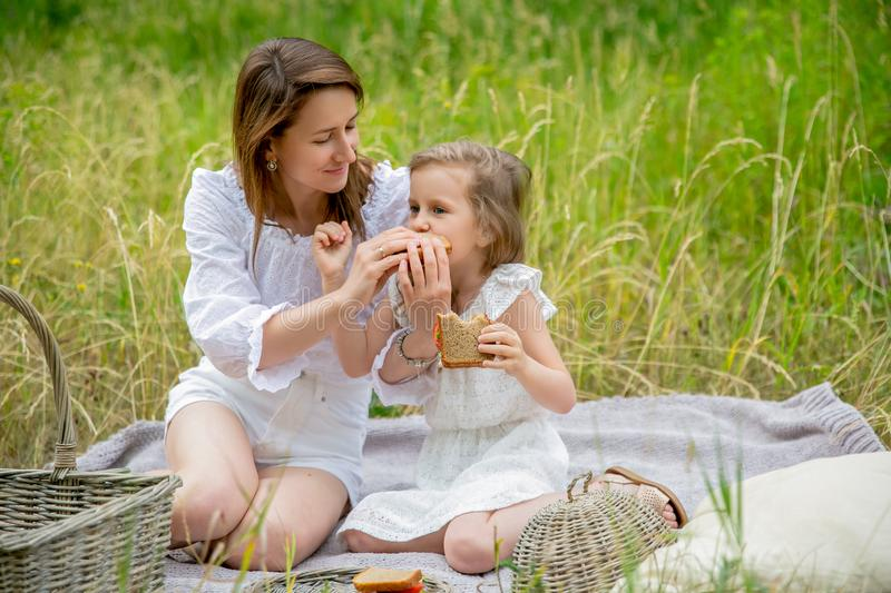Thirty-year-old beautiful young mother and her little daughter in white dress having fun in a picnic. They are sitting on a plaid. On the grass eating stock photography