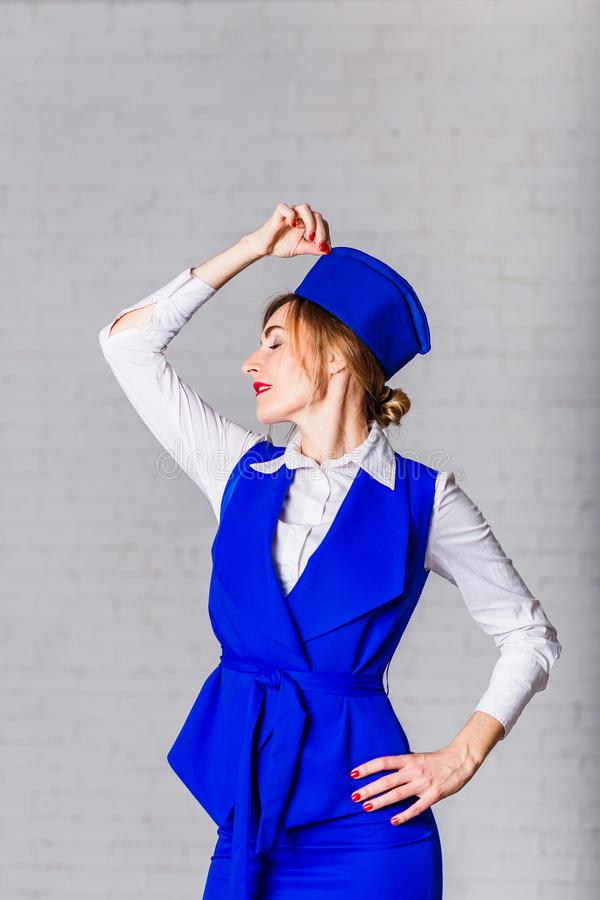 Thirty-year-old happy woman in a blue cap on a white background. Image of stewardess. Female face in profile royalty free stock photo