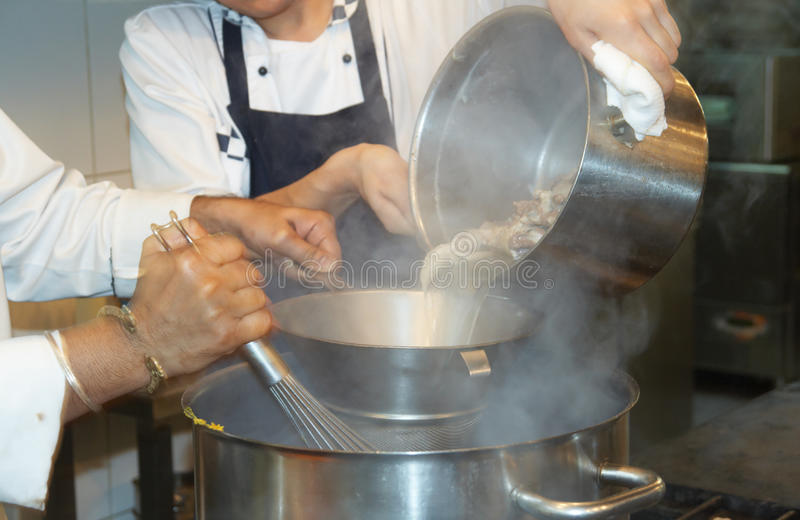 Tho chefs cooking soupe. Two chefs of a restaurant are cooking soup stock images