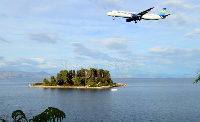 Thomas Cook Airlines Airbus flying over Mouse island and the sea on Corfu, Greece stock image
