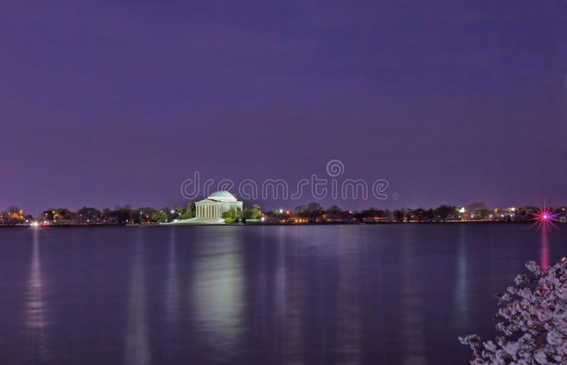 Thomas Jefferson Memorial iluminou na noite com a bacia maré no primeiro plano durante o festival máximo da flor de cerejeira fotografia de stock