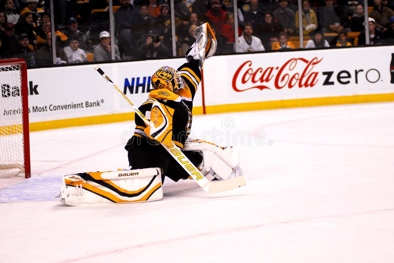 Thomas makes the Save. Boston Bruins Goalie Tim Thomas extends as far as he can to make a glove save royalty free stock image