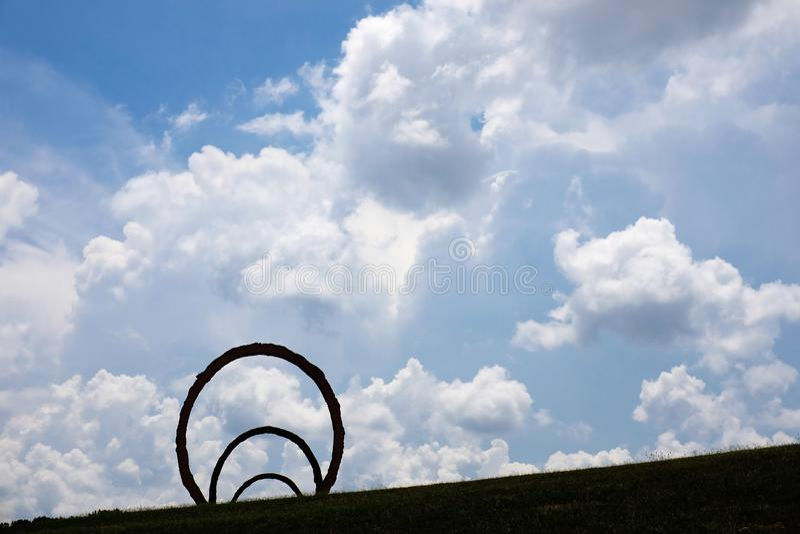 Thomas Sayres 'Drehungs'Skulptur silhouettiert gegen drastische Wolken stockfotografie