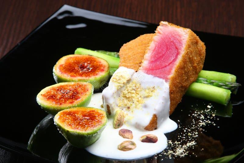 Thon avec de la sauce blanche et des pistaches, accompagnées de l'asperge et des figues vertes image libre de droits