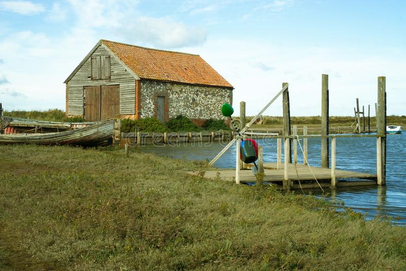 Thornham harbour in Norfolk, Uk. Scene with Jetty, historic barn and old boat at Thornham harbour close to high tide in Norfolk, UK stock photos