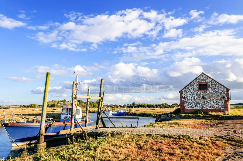 Fishing boats moored on coastal river in marshland, East Anglia, England, United Kingdom. Thornham, Norfolk, England, United Kingdom - October 12, 2012: Fishing royalty free stock images