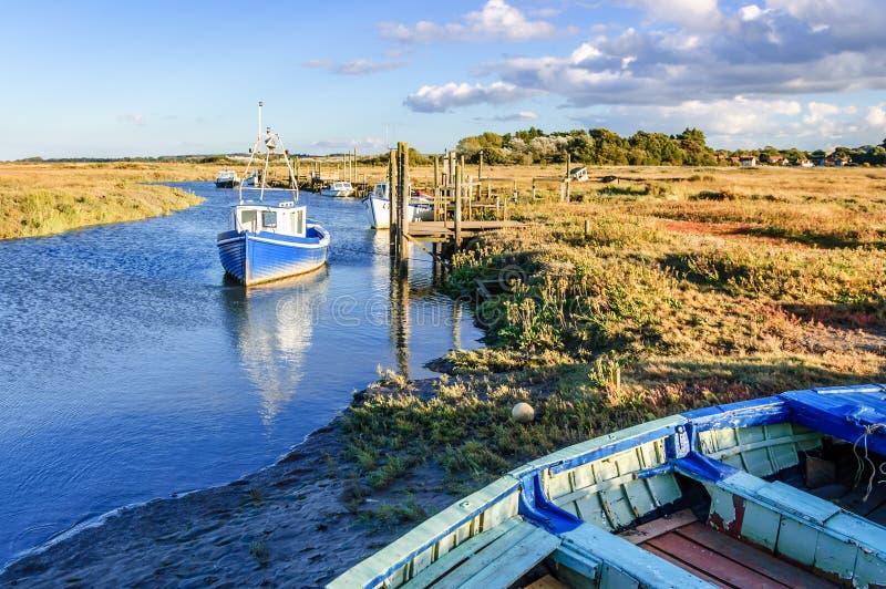 Fishing boats moored on coastal river in marshland, East Anglia, England, United Kingdom. Thornham, Norfolk, England, United Kingdom - October 12, 2012: Fishing stock photography