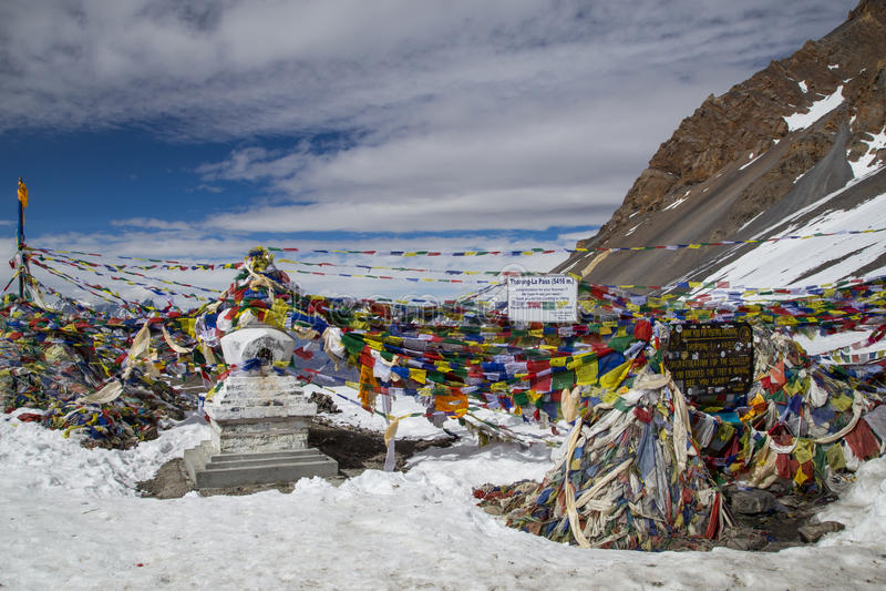 Thorung La Pass on Annapurna Circuit. Photograph of signs and prayer flags on Thorung La Pass on the Annapurna Circuit stock photography