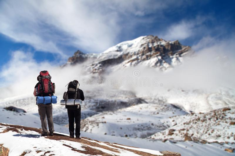 Thorung or Thorong peak with two tourists. The highest point of round Annapurna circuit treking trail, Nepal Himalayas mountains stock photography