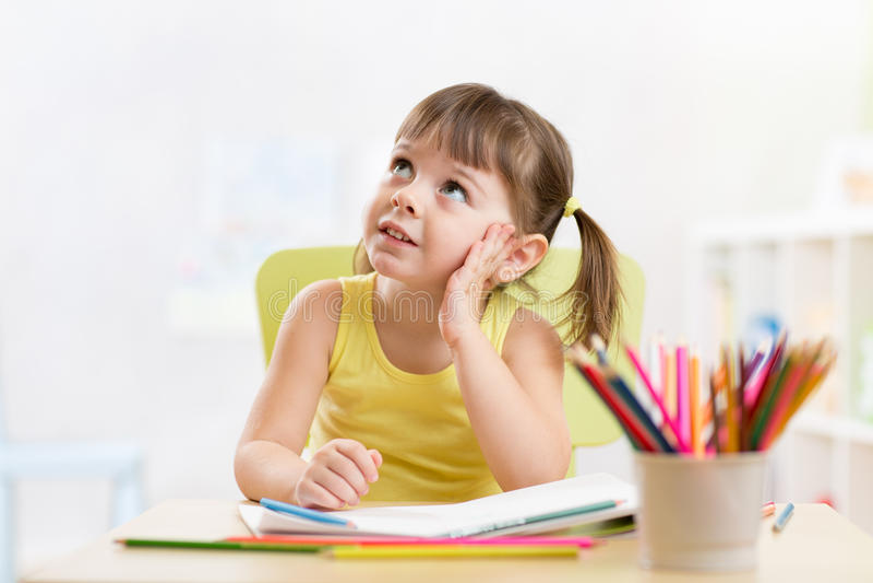 Thoughful儿童与五颜六色的铅笔的女孩图画 免版税图库摄影