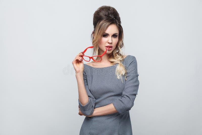Thoughful härlig ung flicka i grå klänning med råttsvansen på huvudanseende och att rymma röda exponeringsglas och att bita monok royaltyfri foto