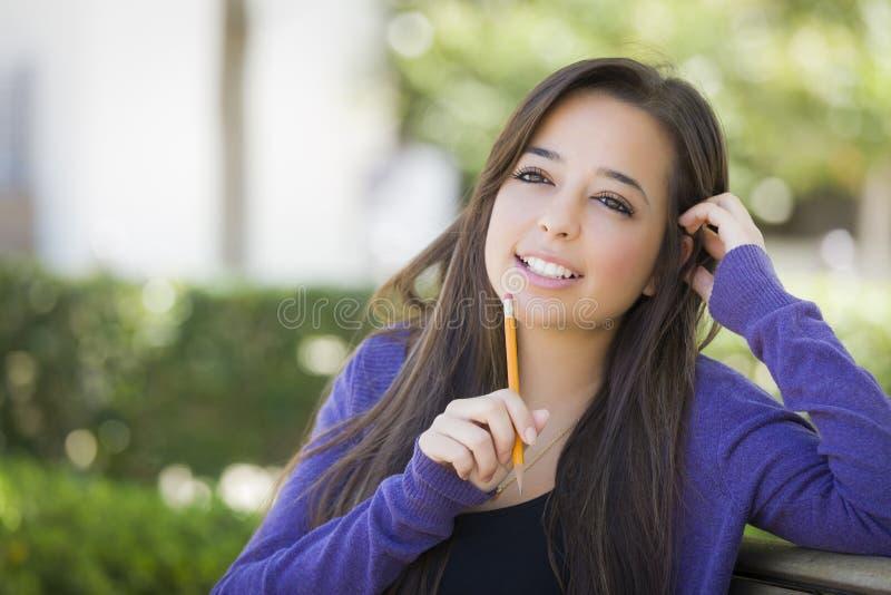 Thoughful-Mischrasse-Studentin mit Bleistift auf dem Campus stockfoto