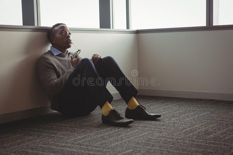 Thoughful wykonawczy sittng na podłoga zdjęcie stock