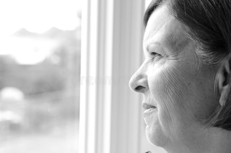 In thought. Image of an older lady in thought while looking out of a window stock photo