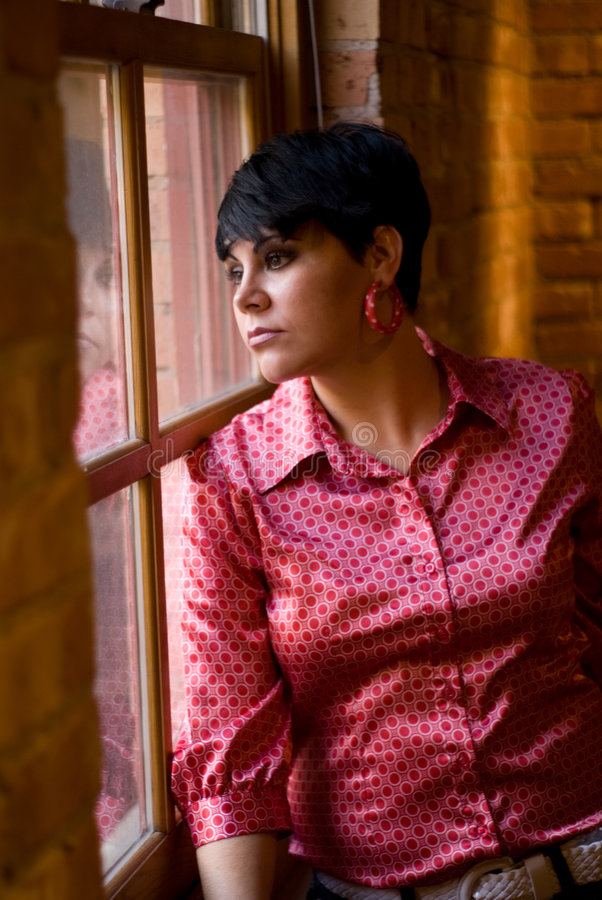 In thought. A beautiful woman gazing out the window, deep in thought stock photography
