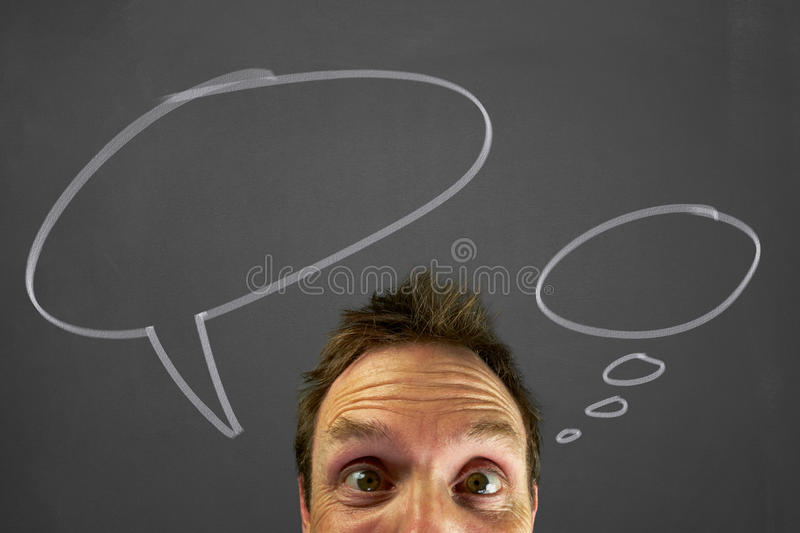 Thought bubbles. Mans head with chalk thought bubbles on a blackboard stock images