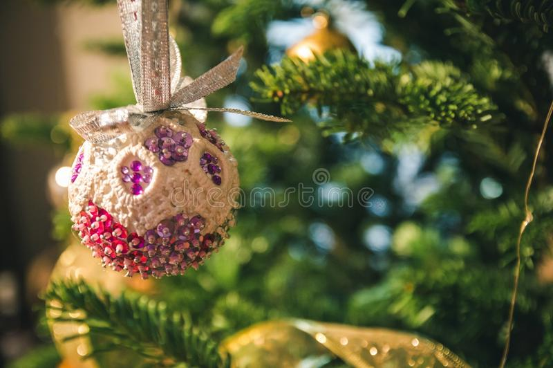 With the thought of christmas. A globe for chistmans tree decoration, made of lace, vibrant colors: magenta, pink, white, silver royalty free stock photo