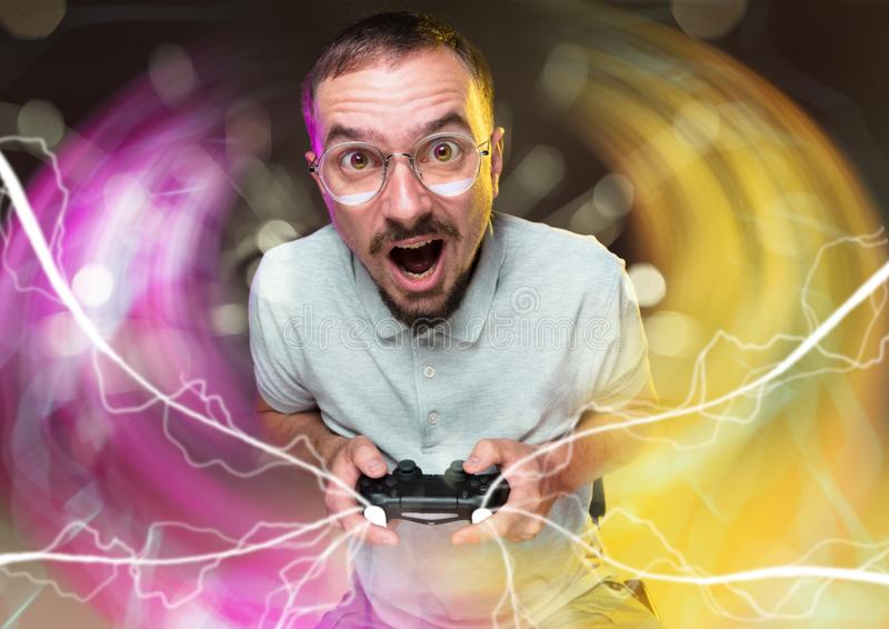 Enthusiastic gamer. Joyful young man holding a video game controller royalty free stock photo