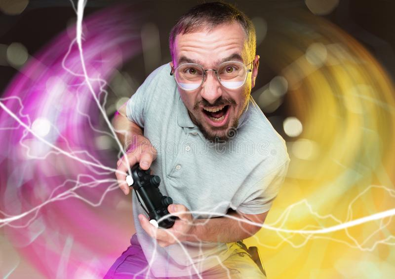 Enthusiastic gamer. Joyful young man holding a video game controller stock image