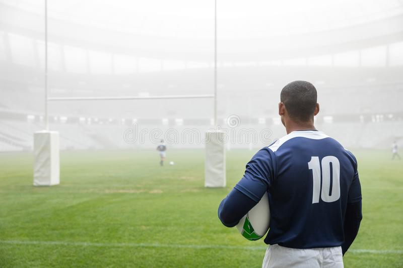 Thoughtful African american male rugby player standing with rugby ball in stadium. Rear view of thoughtful African american male rugby player standing with rugby stock photography
