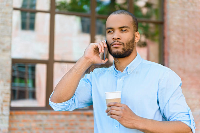 Thoughtful African man communicating on smartphone. Serious young businessman is talking on mobile phone outdoors. He is standing and holding cup of coffee royalty free stock images
