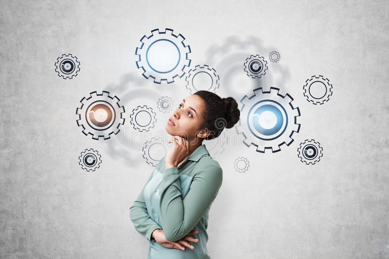 Thoughtful African woman, gears and cogs. Thoughtful young African Amertican woman in green shirt standing near concrete wall with gears drawn on it. Concept of stock photography