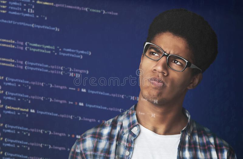 Thoughtful Afro Guy in glasses Looking at strange code royalty free stock image