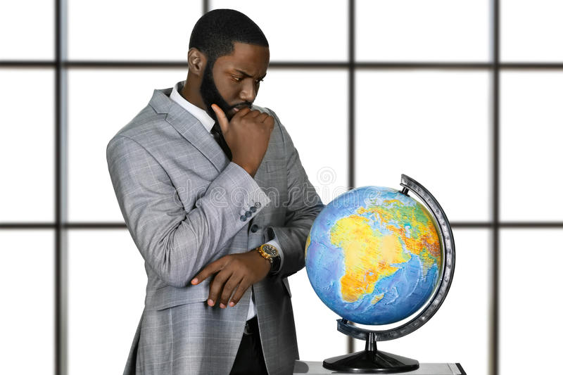 Thoughtful afro man with globe. royalty free stock images
