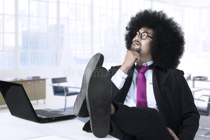 Thoughtful Afro manager in the office royalty free stock photo