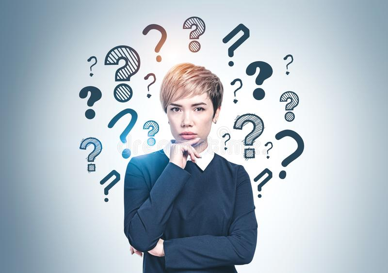 Thoughtful Asian businesswoman, question marks royalty free stock image