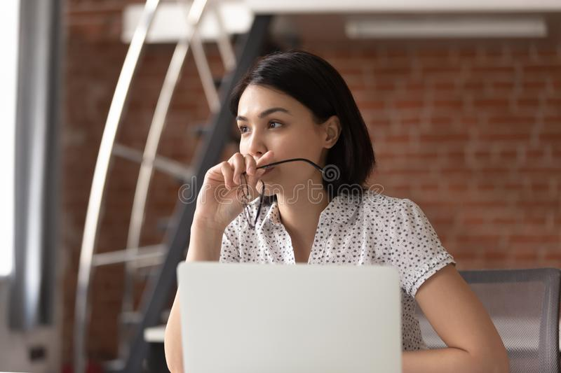 Thoughtful Asian businesswoman taking off glasses, pondering ideas. Developing business strategy, looking in distance, using laptop, pensive employee taking stock photo