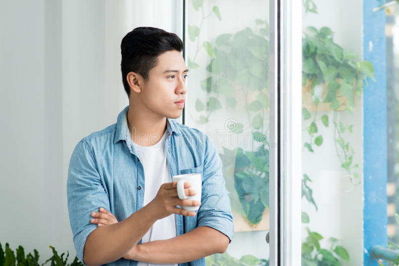 Thoughtful asian man looking out the window in bedroom at home stock images