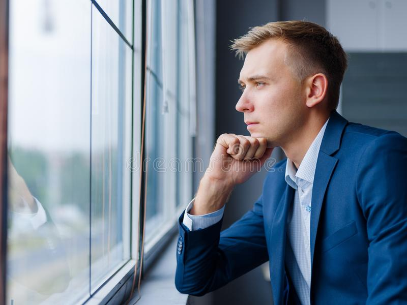 Beautiful business man looking in the window on a blurred background. Business concept. Copy space. royalty free stock photos