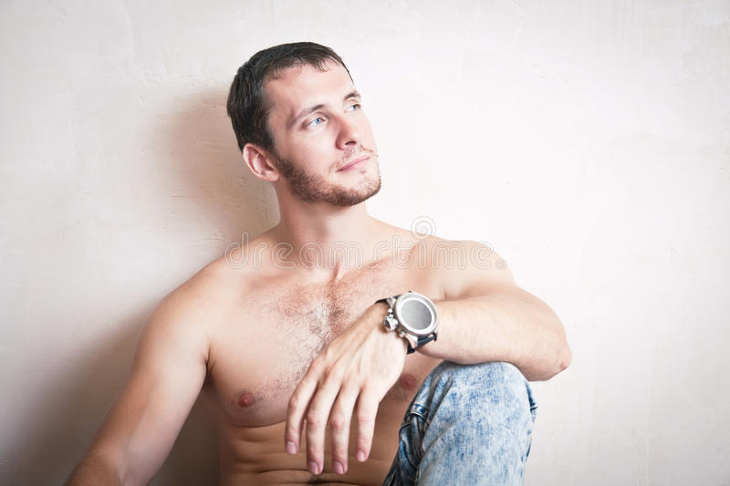 Thoughtful attractive man sitting on the floor stock photography