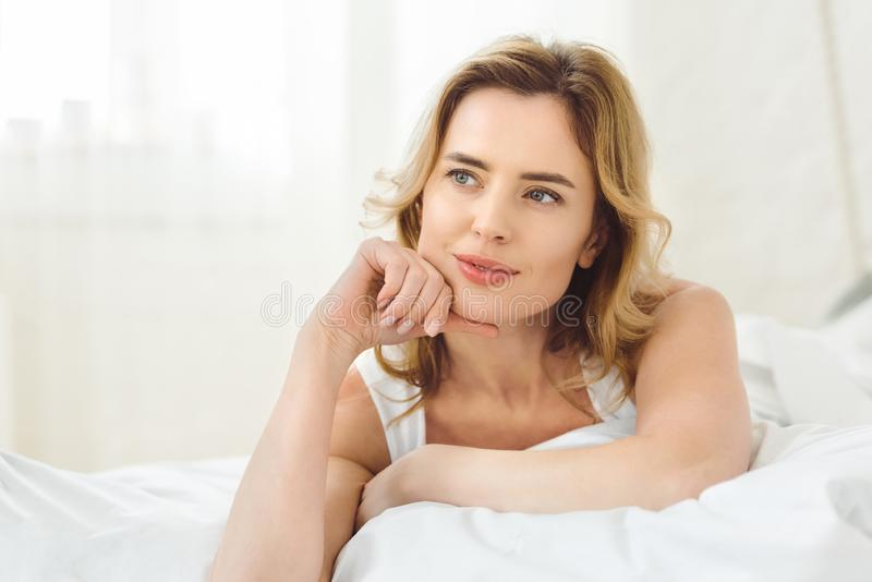 thoughtful attractive woman lying in bed stock images
