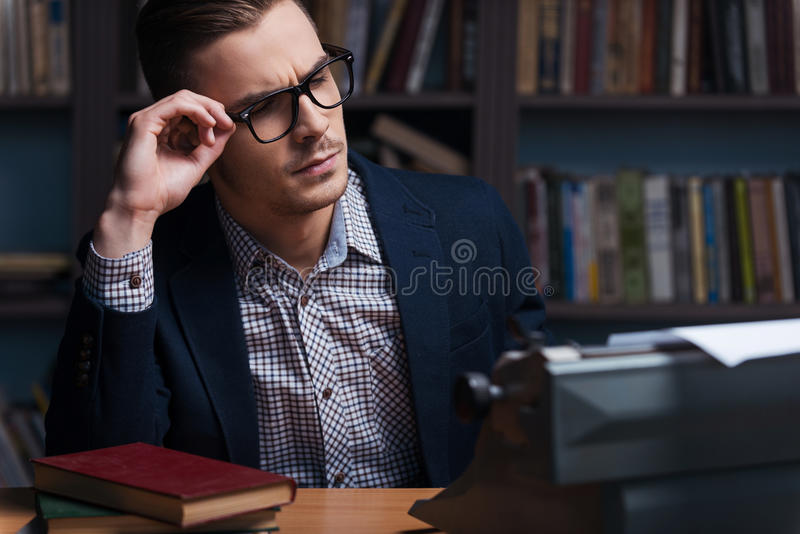Thoughtful author. Thoughtful young author working at the typewriter and adjusting his eyeglasses while sitting at his working place with bookshelf in the royalty free stock photo