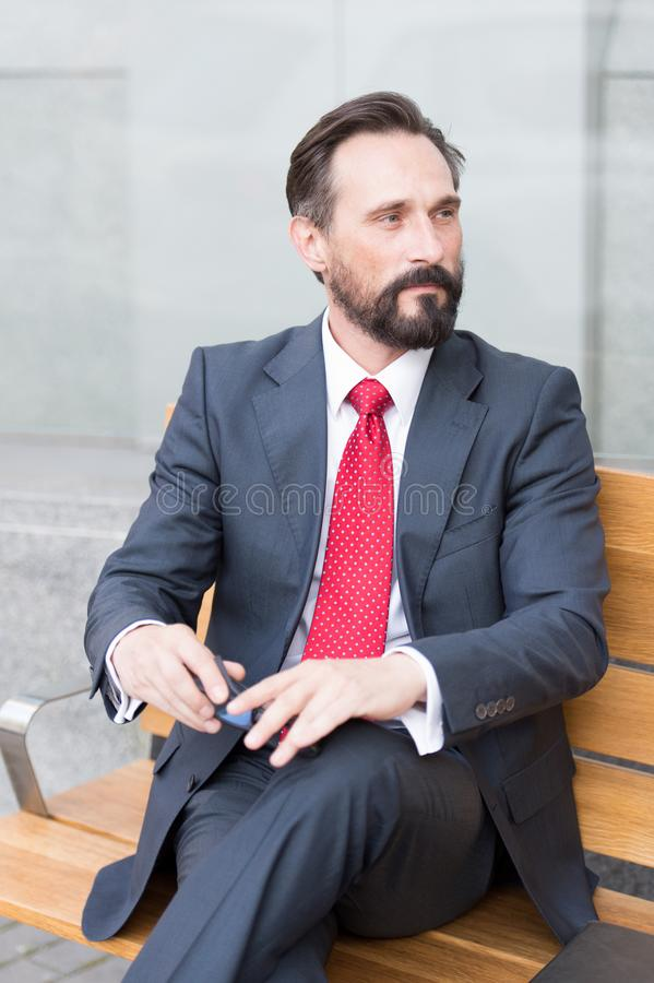 Thoughtful bearded businessman looking away while resting on bench. Contemplations. Calm bearded businessman looking thoughtfully into the distance while holding royalty free stock photos