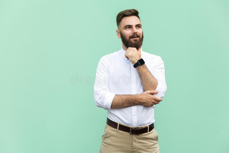 Thoughtful bearded businessman looking away while standing against light green wall. Studio shot royalty free stock photo