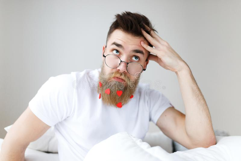 Thoughtful bearded male with trendy hairstyle, mustache and beard, looks pensively upwards through spectacles, plans his royalty free stock photography