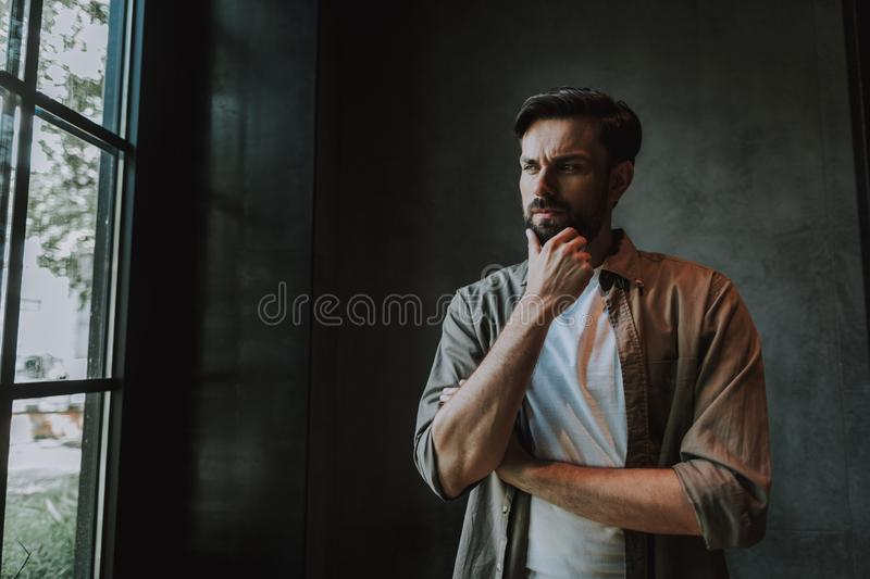 Thoughtful bearded man looking at window indoor royalty free stock photo